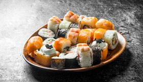 Sushi rolls with salmon and vegetables on a wooden plate. On dark rustic background royalty free stock photo