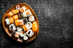 Sushi rolls with salmon and vegetables on a wooden plate. On dark rustic background royalty free stock photos