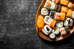 Sushi rolls with salmon and vegetables on a wooden plate. On dark rustic background stock photo