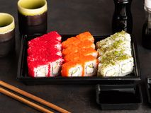 Sushi rolls and sashimi in a black plastic box. Traditional Japanese cuisine with salmon, fish, wasabi, soy sauce, and ginger royalty free stock photography
