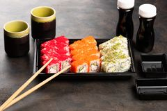 Sushi rolls and sashimi in a black plastic box. Traditional Japanese cuisine with salmon, fish, wasabi, soy sauce, and ginger royalty free stock photos