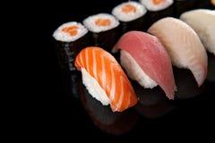 Sushi rolls and sashimi. Set of sushi rolls and sashimi on a black background royalty free stock photography