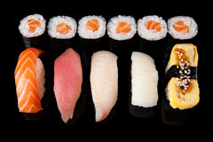 Sushi rolls and sashimi. Set of sushi rolls and sashimi on a black background stock images