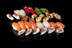 Sushi rolls and sashimi. Set of sushi rolls and sashimi on a black background royalty free stock photo