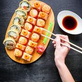 Sushi rolls, sauce, ginger, wasabi and woman hand holding chopsticks on dark background. Top view. Flat lay. Royalty Free Stock Photography