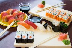Sushi rolls with sauce on plates Royalty Free Stock Photos