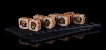 Sushi-rolls with seafood in sesame seeds on plate isolated on black. Background Stock Photography