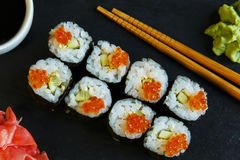 Sushi rolls served on stone slate red caviar Stock Photos