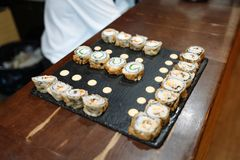 Sushi rolls set on black board on wooden table royalty free stock image
