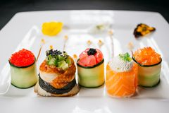 Sushi rolls set, fusion food style restaurant menu. Sushi rolls degustation, fusion food style restaurant menu, deluxe gastronomy. Set of finest seafood snacks royalty free stock photo
