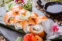 Sushi rolls set with salmon, cream cheese, red caviar, avocado and wasabi on black stone on bamboo mat. Selective focus. Japanese cuisine stock image