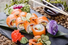 Sushi rolls set with salmon, cream cheese, red caviar, avocado and wasabi on black stone on bamboo mat, selective focus. Japanese cuisine royalty free stock photos