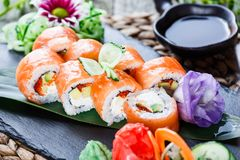 Sushi rolls set with salmon, cream cheese, red caviar, avocado and wasabi on black stone on bamboo mat, selective focus. stock image