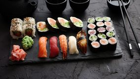 Sushi rolls set with salmon and tuna fish served on black stone board stock video
