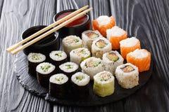 Sushi rolls set with sauces served on black slate on dark backgr Stock Photos