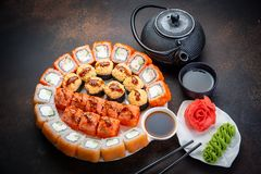 Sushi rolls set served on black stone slate on dark background. Japanese menu. Horizontal top view from above royalty free stock photo