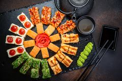 Sushi rolls set served on black stone slate on dark background. Japanese menu. Horizontal top view from above royalty free stock photography