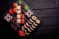 Sushi rolls set served with wasabi and ginger on a black wood table stock photo