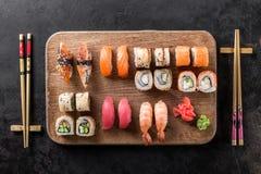 Sushi rolls set served on wooden board. On dark background Stock Images