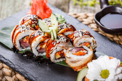 Sushi rolls set with smoked eel, red caviar, sesame and wasabi on black stone on bamboo mat, selective focus. Royalty Free Stock Images