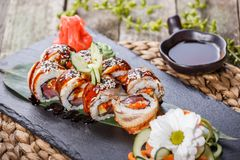 Sushi rolls set with smoked eel, red caviar, sesame and wasabi on black stone on bamboo mat. Selective focus. Japanese cuisine stock photos