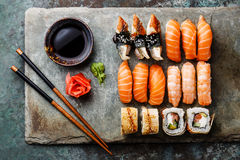 Sushi rolls set on stone slate. Sushi rolls set served on gray stone slate on metal background stock photos