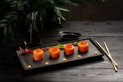 Sushi rolls set with tuna on a black plate on a black wooden background royalty free stock photos