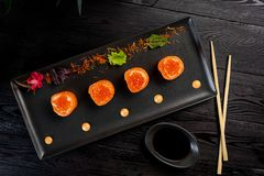Sushi rolls set with tuna on a black plate on a black wooden background royalty free stock photography