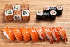 Sushi rolls set with tuna and smoked eel and sesame  on the wooden background Royalty Free Stock Photography