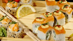 Sushi rolls set on a wooden board close up. rotating on black backround stock footage