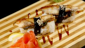 Sushi rolls set on a wooden board. rotating on black backround stock footage