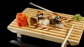 Sushi rolls set on a wooden board. rotating on black backround stock video footage