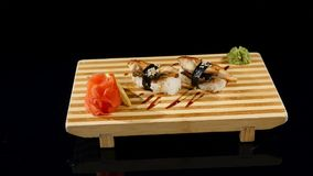 Sushi rolls set on a wooden board. rotating on black backround stock video