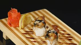 Sushi rolls set on a wooden board. rotating on black backround.  stock footage