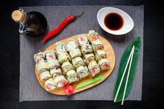 Sushi rolls, soy sauce, ginger and chopsticks on dark background. Top view. Flat lay. Royalty Free Stock Images