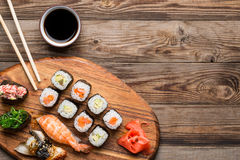 Sushi, rolls and spices on wooden light brown background Stock Photos