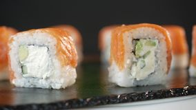 Sushi rolls spin in a circle then stop and one roll is taken with the help of chopsticks. Tasty fast food. stock video