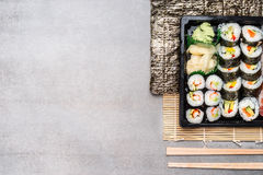 Sushi rolls in transport box with chopsticks on stone slate background, top view Stock Photo