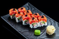 Sushi rolls with tuna and caviar. On a black plate stock photos