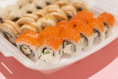 Sushi rolls in a white plastic lunch box takeaway royalty free stock image