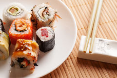Sushi rolls on a white plate with chopsticks, closeup Stock Photos