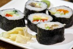 Sushi rolls on a white plate with soy sauce. Against the backdrop of a vintage wooden table stock image
