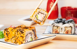 Sushi rolls on the white plate on wooden background Royalty Free Stock Image