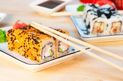 Sushi rolls on the white plate on wooden background Royalty Free Stock Photography