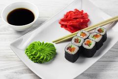 Sushi rolls on a white square plate with wasabi, soy sauce and ginger. white wooden background.  royalty free stock photo