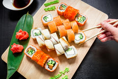 Sushi rolls on wood board, sauce, ginger, wasabi and hand holding chopsticks on dark background. Top view. Flat lay. Stock Images
