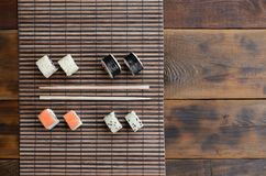 Sushi rolls and wooden chopsticks lie on a bamboo straw serwing mat. Traditional Asian food. Top view.  stock photo