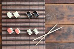 Sushi rolls and wooden chopsticks lie on a bamboo straw serwing mat. Traditional Asian food. Top view.  royalty free stock images