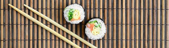 Sushi rolls and wooden chopsticks lie on a bamboo straw serwing mat. Traditional Asian food. Top view. Flat lay minimalism shot. With copy space stock photo
