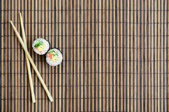 Sushi rolls and wooden chopsticks lie on a bamboo straw serwing mat. Traditional Asian food. Top view. Flat lay minimalism shot. With copy space stock images